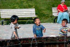 Inuit Kids Playing in a Fountain on a Summer Day in Greenland